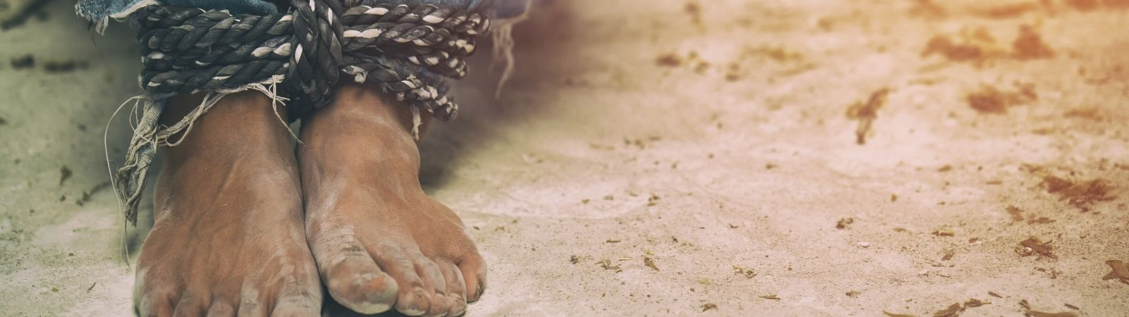 Child's bare feet in sand with rope tied around his legs to symbolize human trafficking.