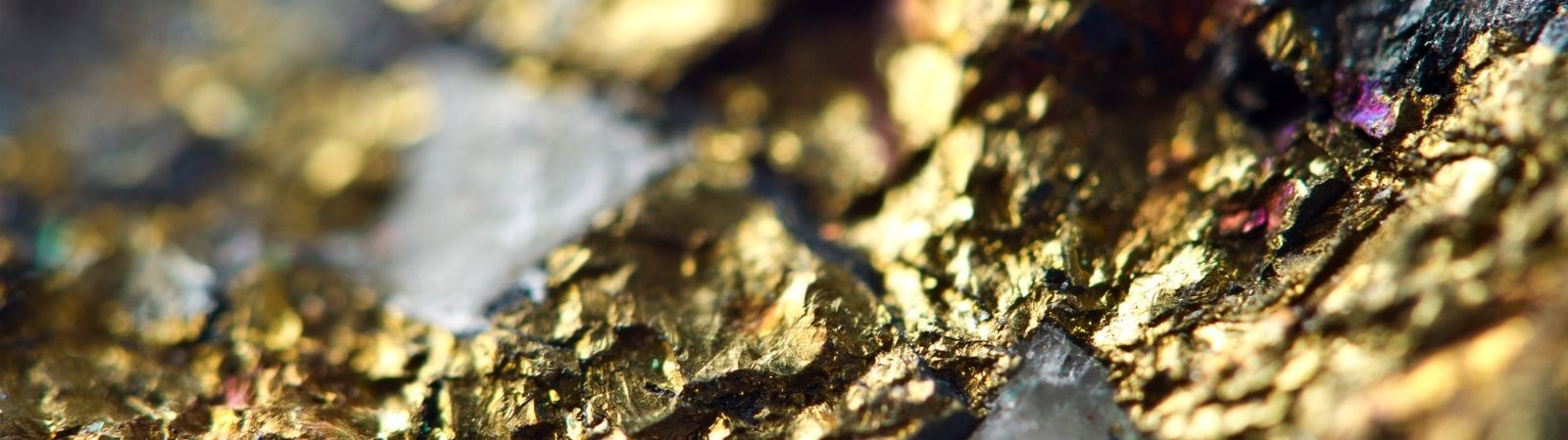 Close up of the conflict mineral gold in its raw, unrefined state mixed with dark stone.