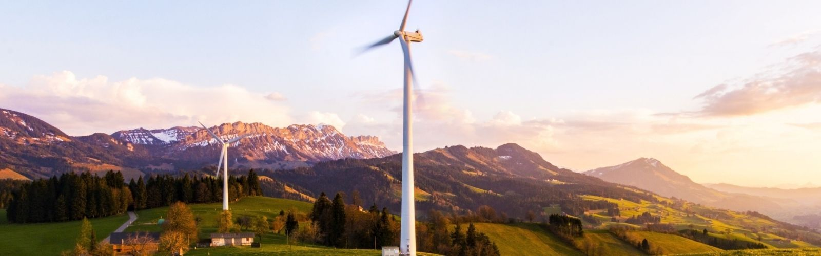 Mountain scape at sunset with modern white windmills, symbolizing clean energy and ESG