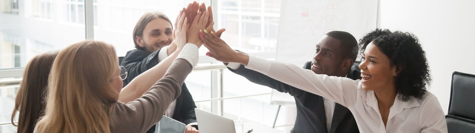Happy business meeting with five smiling, diverse professionals high-fiving signifying collaboration.