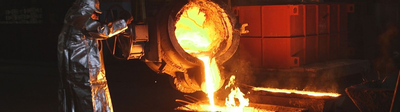 Smelter employee in a silver protective hazmat suit pouring molten gold from a heavy industrial pot into a container on the ground.