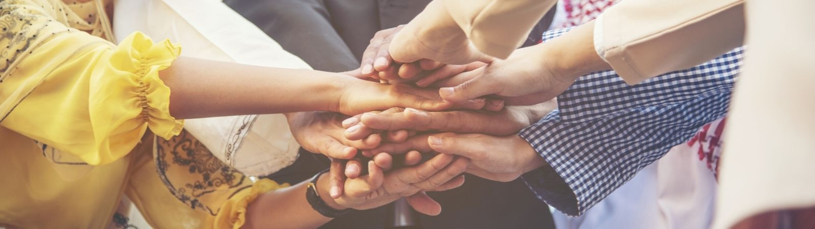 Diverse professionals from around the globe putting hands in the middle of a huddle to symbolize working together and supplier diversity.