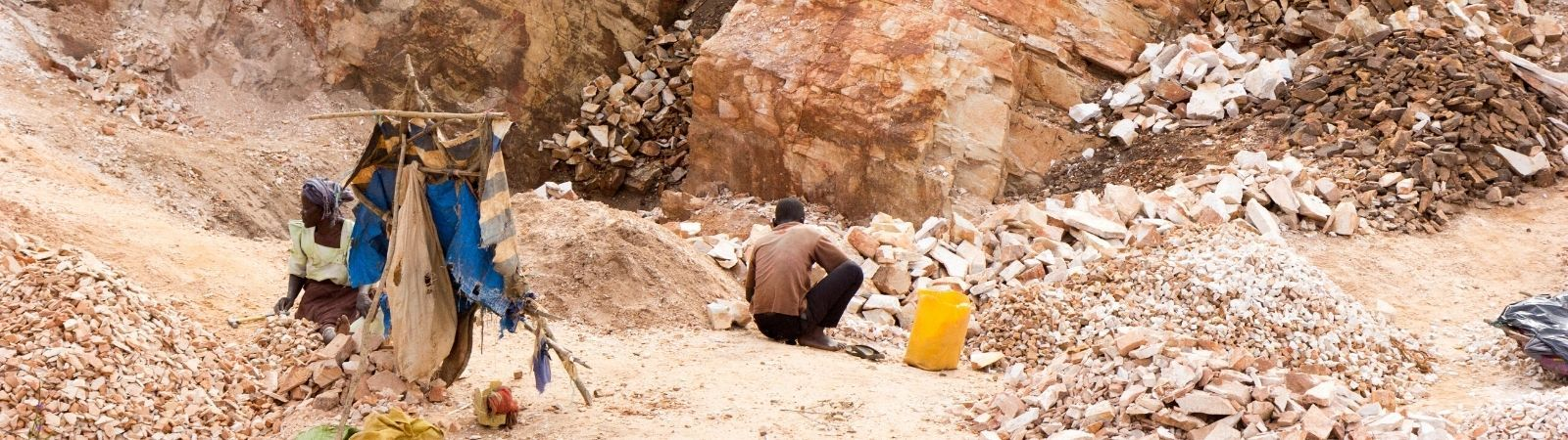 Desert mine on a relentlessly sunny day using modern day slavery with workers in tattered clothes.